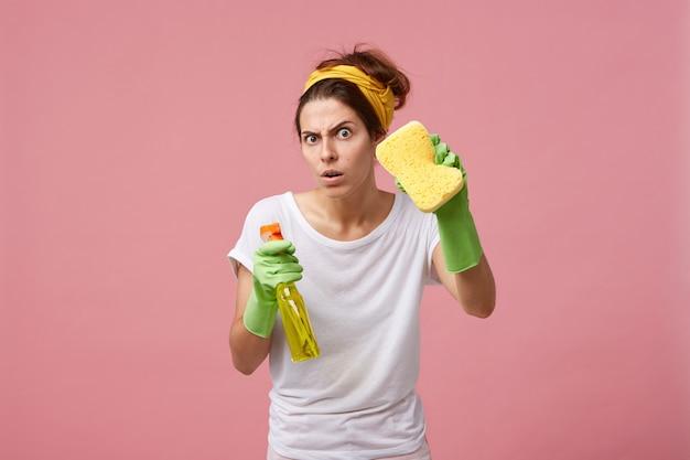 黄色のスポンジとスプレー洗剤を備えた緑のゴム手袋でポーズをとる感情的なかわいい女性は、彼女の顔に面白い表情で掃除をして家を掃除する準備ができています 無料写真
