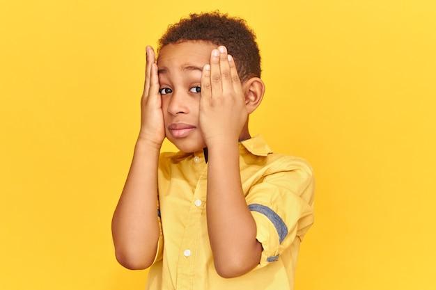 Emotivo bambino dalla pelle scura tenendo le mani sulle guance avendo sconvolto sguardo smemorato, stressato a causa dei brutti voti a scuola. Foto Gratuite
