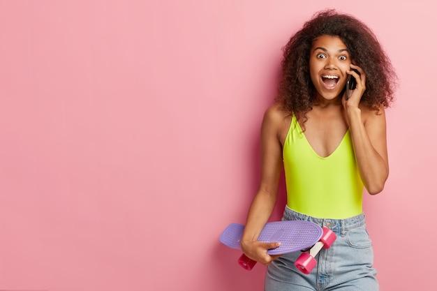 Эмоциональная темнокожая женщина разговаривает по мобильному телефону, рассказывает новости другу, одетая в модную летнюю одежду, держит лонгборд, стоит у розовой стены, копирует пространство в стороне. концепция образа жизни Бесплатные Фотографии