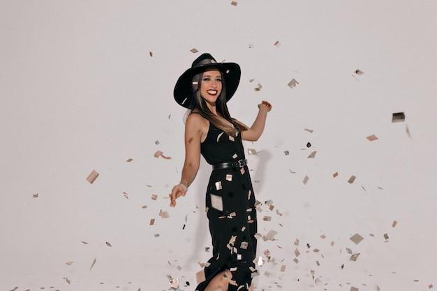Emotiva donna elegante che indossa il cappello che celebra la festa in elegante abito nero. ragazza efficace che mostra il suo bel sorriso e balli Foto Gratuite