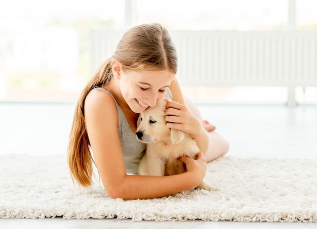 Emotional girl hugging retriever puppy Premium Photo