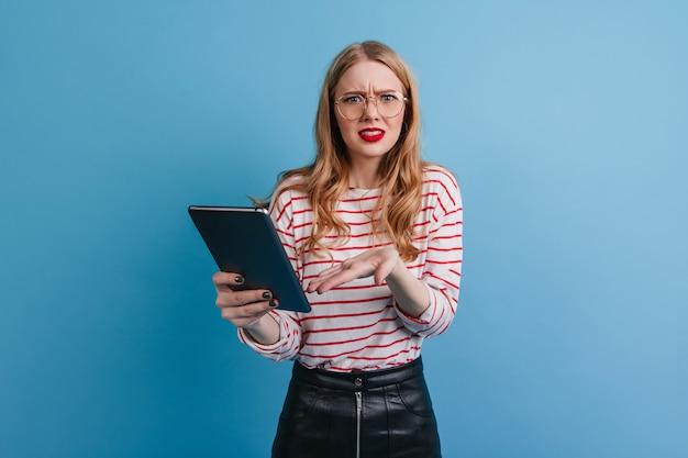 Ragazza emotiva in camicia a righe utilizzando la tavoletta digitale. studio shot di caucasica donna bionda con gadget isolato su sfondo blu. Foto Gratuite