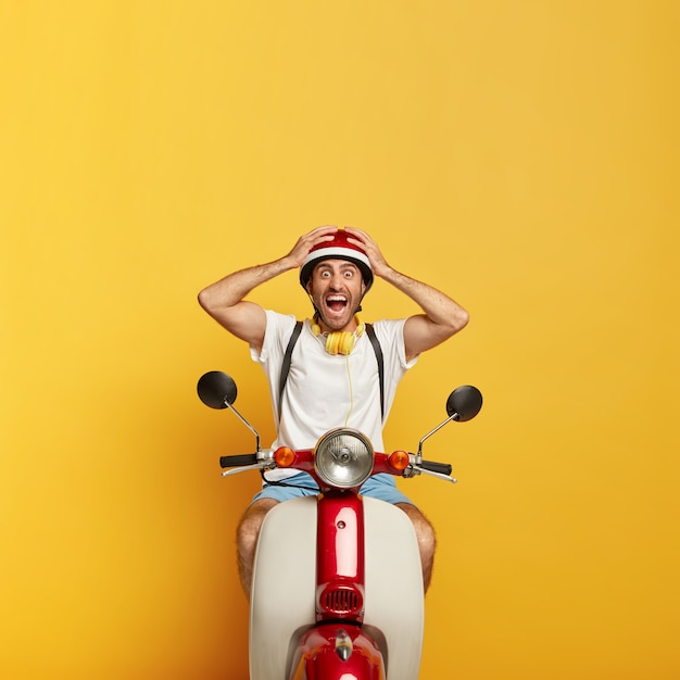 Emotional handsome male driver on scooter with red helmet Free Photo