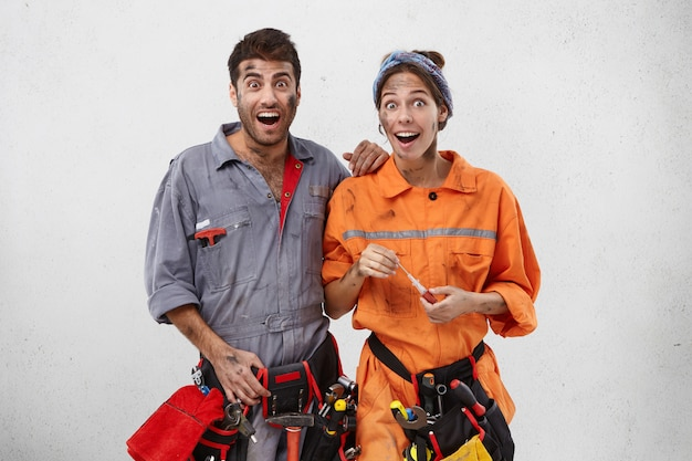 Emotional happy female and male carpenters look with excitement or surprisment Free Photo