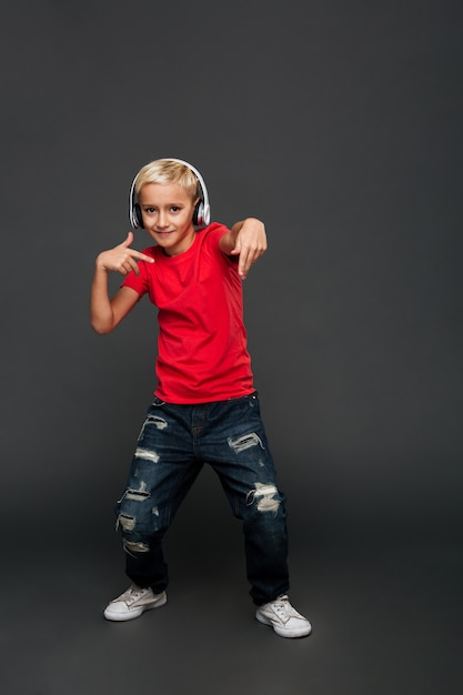 Emotional little boy child listening music with headphones dancing. Free Photo