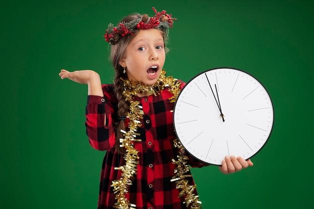 Bambina emotiva che indossa la corona di natale in abito controllato con orpelli intorno al collo che tiene l'orologio da parete guardando la telecamera stupito e sorpreso con il braccio alzato in piedi su sfondo verde Foto Gratuite