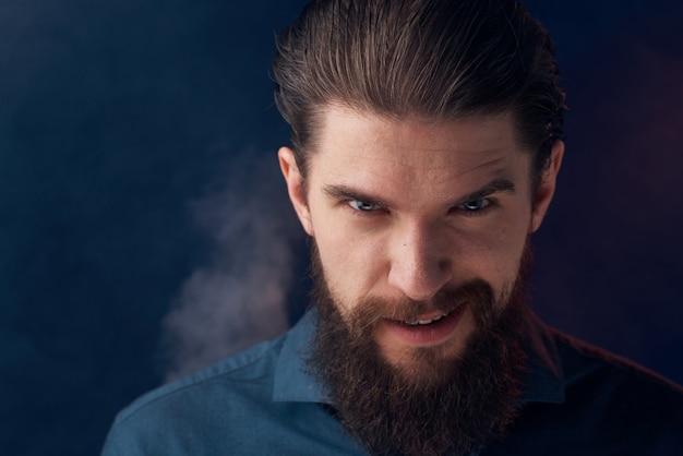 感情的な男の黒いシャツの魅力的な外観のクローズアップの煙が背景にあります。高品質の写真 Premium写真
