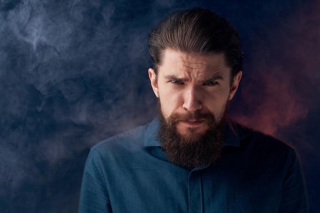 感情的な男の黒いシャツの魅力的な外観のクローズアップの煙が背景にあります。 Premium写真