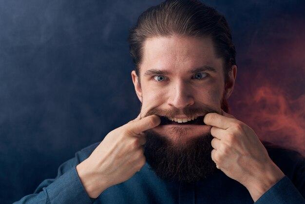 感情的な男の黒いシャツの魅力的な外観のクローズアップの煙が壁に Premium写真