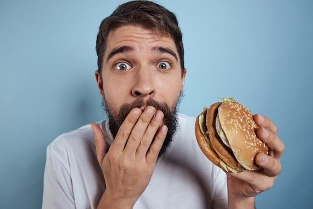 感情的な男のハンバーガーファーストフードダイエット食品クローズアップ青い背景。高品質の写真 Premium写真