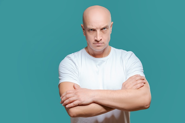 Emotional man in white t-shirt with angry facial expression on background Premium Photo