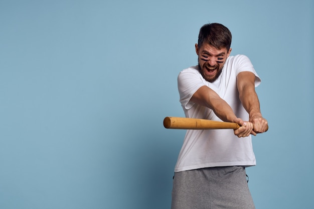 Emotional man with a bat in his hand on a blue space and makeup on his face black lines energy t-shirt baseball. Premium Photo