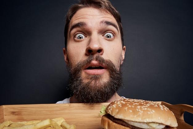 ハンバーガーとフライドポテトと感情的な男 Premium写真
