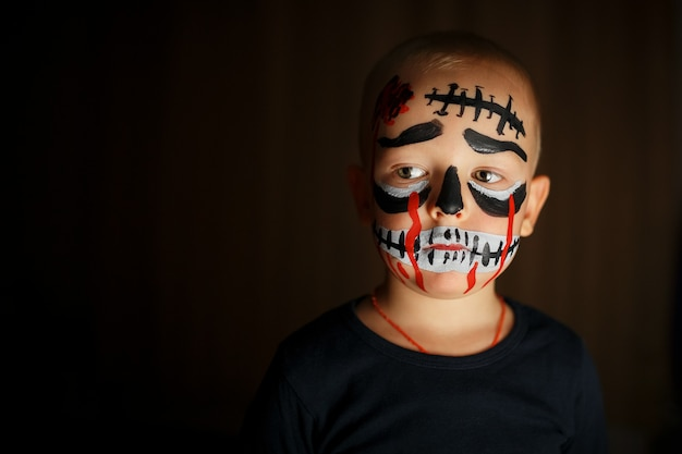 Emotional portrait of a boy with a scary zombie on his face Premium Photo