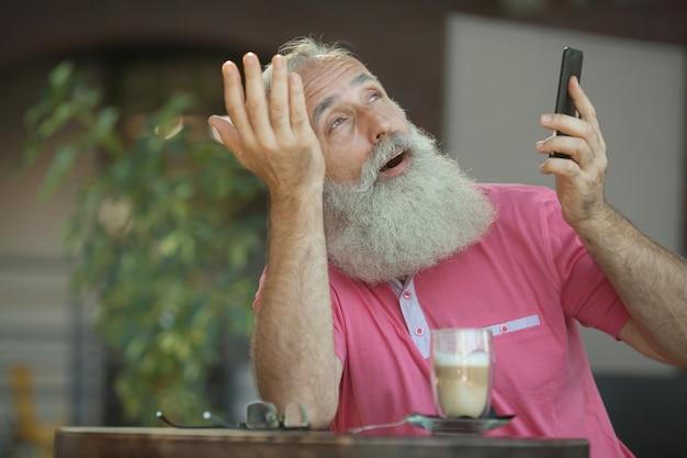 Эмоциональный портрет веселого и стильного зрелого делового человека с лысой головой, с улыбкой разговаривающей на смартфоне с другом. бородатый старший мужчина Premium Фотографии