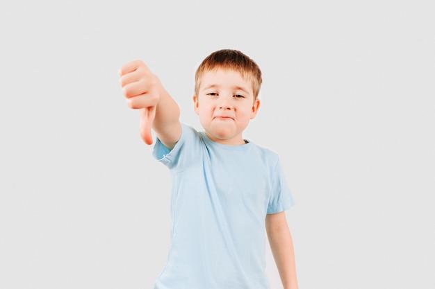 Эмоциональный портрет малыша мальчика, давая пальцы вниз жест рукой Premium Фотографии