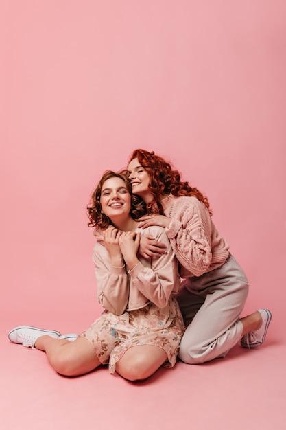 Belle ragazze impressionabili che si siedono su fondo rosa. due amici che si abbracciano mentre posa sul pavimento. Foto Gratuite