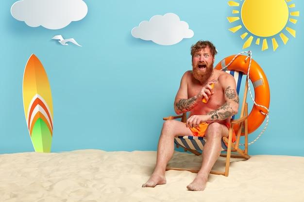선크림과 함께 해변에서 포즈를 취하는 감정적 인 빨간 머리 무료 사진