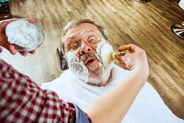 Uomo senior emotivo visitando parrucchiere nel negozio di barbiere Foto Gratuite