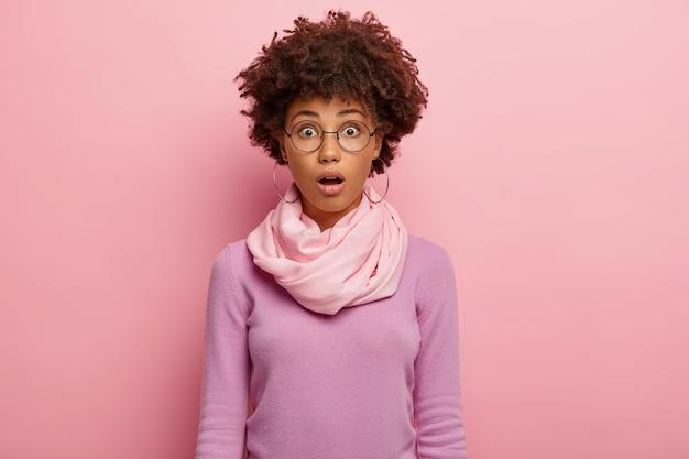 곱슬 아프로 헤어 스타일을 가진 감정적 인 혼란스러운 여성, 입을 벌리고 둥근 안경, 캐주얼 점퍼를 착용하고 의아해 뉴스에 충격을 받고 경이로움에서 입을 열었습니다. 무료 사진