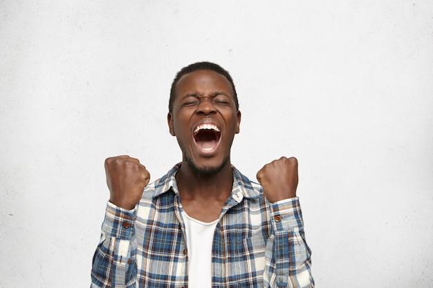 感情的に成功した幸運なアフリカ系アメリカ人男性。口を大きく開いて目を閉じて悲鳴を上げ、予想外に宝くじに当たった後、応援しながら拳を握り締めました。人間の感情と感情 無料写真