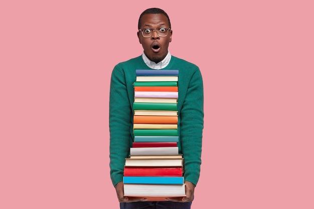 감정적 인 놀란 흑인 남자는 겁에 질린 표정으로 보이고, 교과서 더미를 들고, 준비해야 할 많은 작업이 두려워, 분홍색 배경 위에 모델 무료 사진