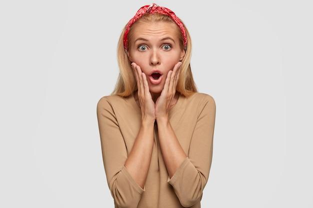 感情的な驚きのブロンドの女性は手のひらで頬に触れ、赤いヘッドバンドとベージュのセーターを着ています 無料写真