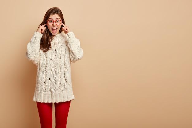 La femmina emotiva sorpresa arriva alla festa rumorosa, insoddisfatta della musica, tappi le orecchie, evita il rumore, grida di fermarsi, indossa un maglione casual, collant rossi, posa sul muro beige. omg è troppo rumoroso qui Foto Gratuite