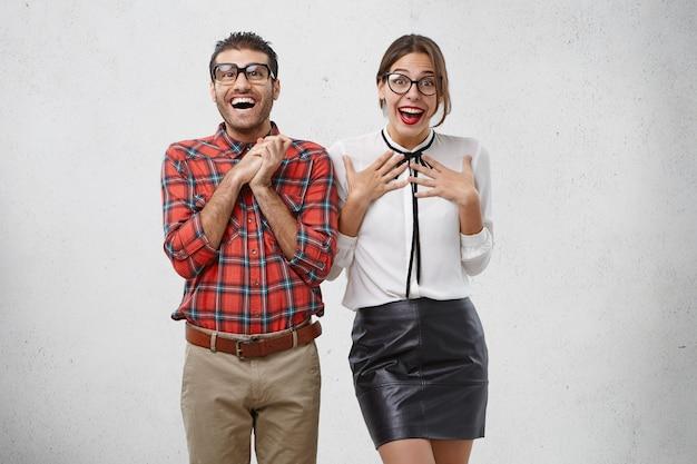 感情的に驚いた幸せな女と男は眼鏡をかけ、信じられないほどの表情を持っています 無料写真