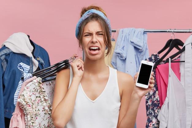 感情的な不幸な女性は、彼女が銀行の会計士に楽屋に立って、コピースペーススクリーンで携帯電話を保持しているファッショナブルな高価な服を買うお金がないので、欲求不満を感じて泣いています。 無料写真