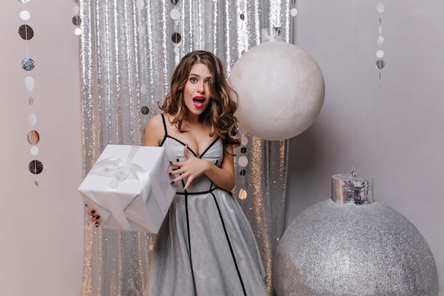 Эмоциональная белая женщина в длинном вечернем платье позирует с изумлением, держа в руках большую настоящую коробку. очаровательная женская модель в блестящей одежде стоит возле огромных елочных игрушек с подарком. Бесплатные Фотографии