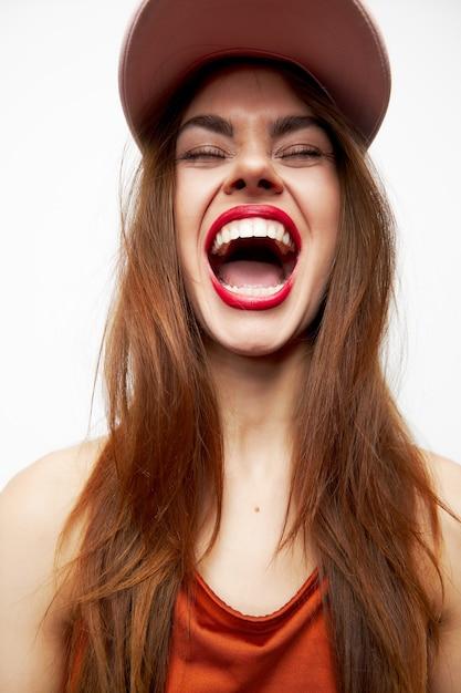 Эмоциональная женщина в кепке эмоции веселье смех закрытые глаза вечерний макияж обрезанный вид Premium Фотографии