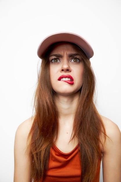 帽子をかぶった感情的な女性贅沢の生意気な表情はその唇を噛みます Premium写真
