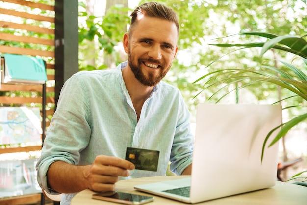 クレジットカードを保持しているラップトップを使用して感情的な若いひげを生やした男。 Premium写真