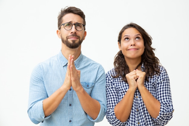 Emotional young couple praying together Free Photo