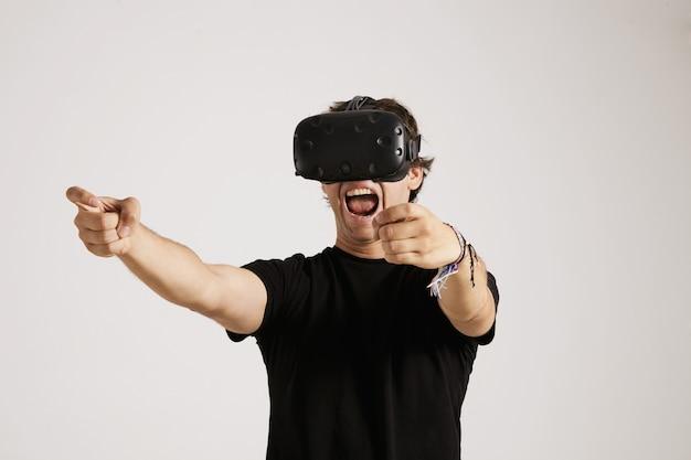 Un giovane giocatore emotivo con un visore vr e una maglietta nera senza etichetta urla mentre gioca Foto Gratuite