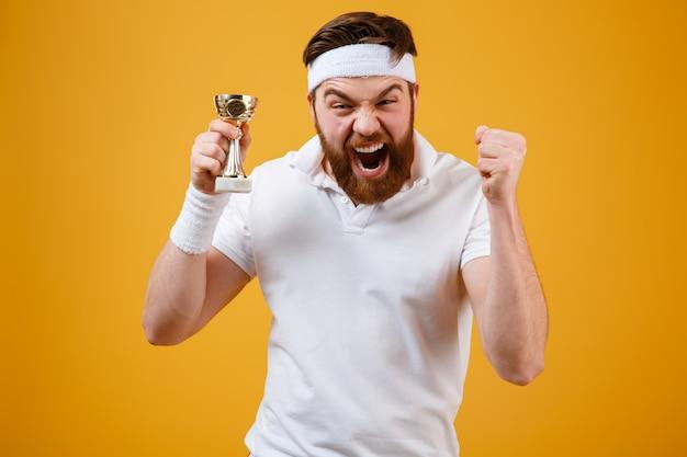 報酬を保持している感情的な若いスポーツマンは勝者のジェスチャーを作ります。 無料写真