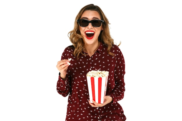 Emotional young woman with popcorn watching blockbuster movie in stereo glasses Free Photo