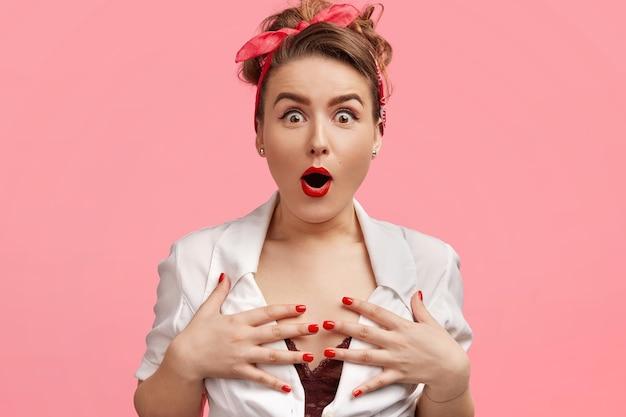 Una splendida signora emotiva tiene le mani sul seno, fissa con gli occhi spalancati e il fiato sospeso, non riesce a credere in qualcosa di straordinario, indossa una fascia rossa, ha le labbra dipinte di rosso e la manicure, isolata sul rosa Foto Gratuite