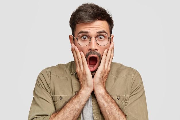 口を大きく開けた感情的な怖いショックを受けた男性は、印象的な噂を聞き、唖然とした表情で見つめ、昏迷し、丸い眼鏡をかけ、白い壁に隔離されます 無料写真