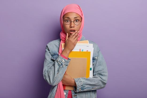 Эмоциональная ошеломленная темнокожая мусульманка в хиджабе открывает рот от удивления, держит в руках какие-то бумаги и блокноты. Бесплатные Фотографии