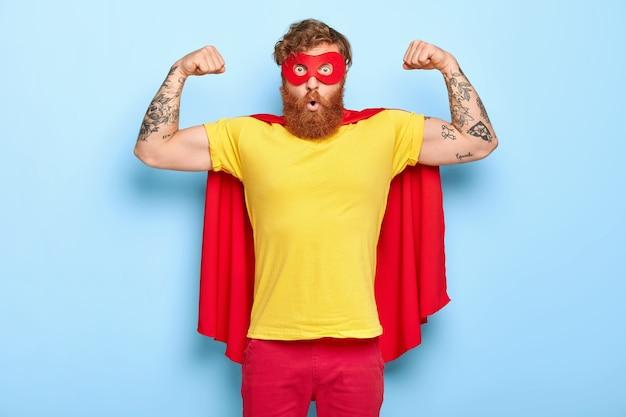 Эмоционально удивленный герой-мужчина обладает благородными качествами, демонстрирует силу с поднятыми руками. Бесплатные Фотографии