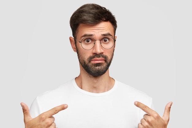 濃い黒ひげを持つ感情的な若いハンサムな男、戸惑いの空白のtシャツを指しています 無料写真