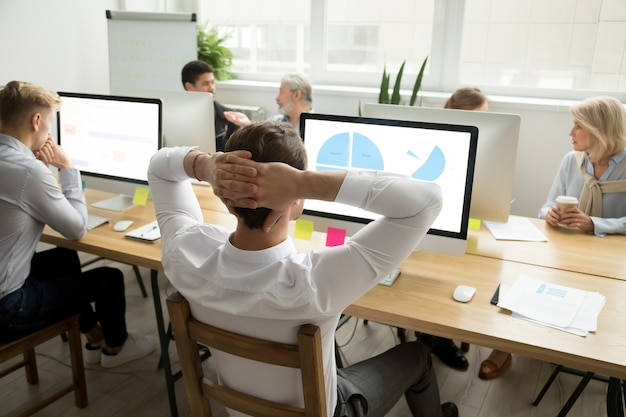 Employee analyzing statistics report sharing office desk with diverse colleagues Free Photo