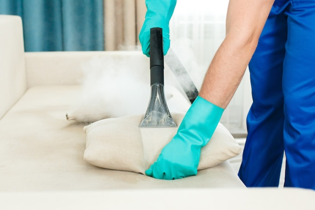 An employee of a cleaning company provides a chemical and steam cleaning service for the sofa. | Premium Photo