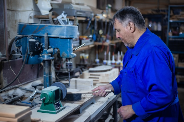 Employee drills the item in the workshop with the help of a drilling press Premium Photo