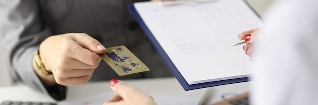Employee gives the client plastic bank card and document for signature banking services concept Premium Photo