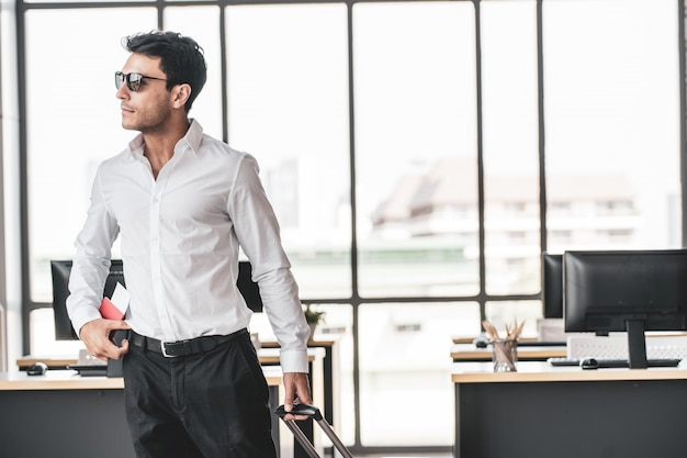 Employee in office ready to travel on summer vacation holidays. Premium Photo