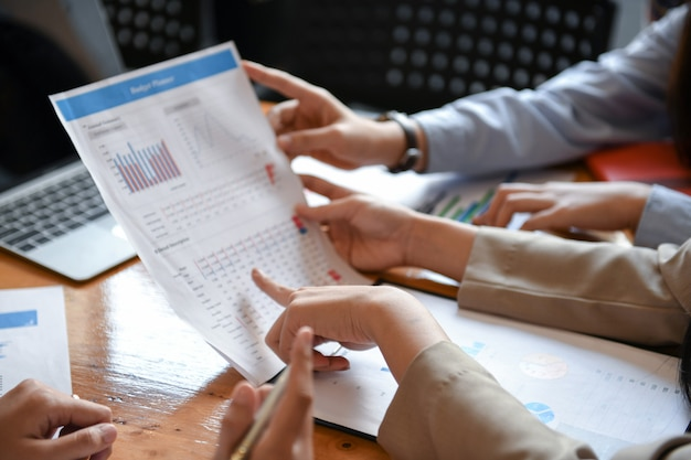 Employees are analyzing data.they use their hands point to graphs. Premium Photo