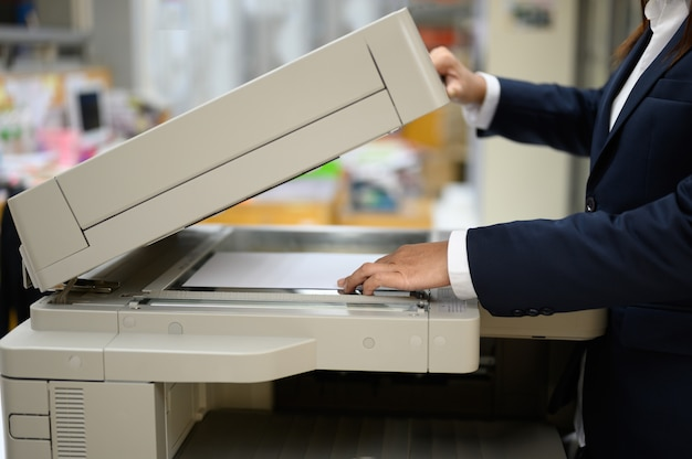 Employees are copying documents with a copy machine at the office. Premium Photo